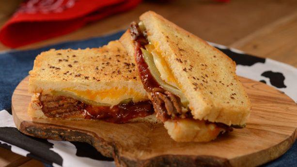 BBQ Brisket Melt – brisket defumado, cheddar, Monterey Jack, picles e molho barbecue em pão grelhado com manteiga de alho.Toy Story Land Woodys Lunch Box Menu